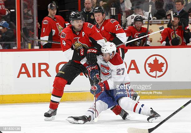 Chris Phillips of the Ottawa Senators shoves Alex Galchenyuk of the Montreal Canadiens to the ice as Chris Neil of the Ottawa Senators looks on...