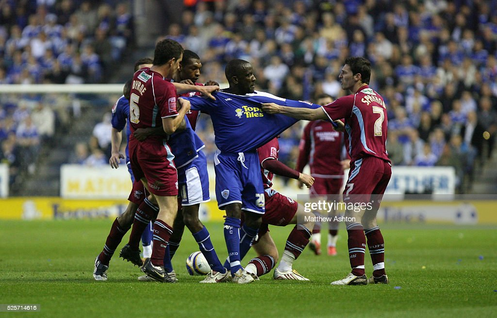 Chris Powell of Leicester City tries to break up a melee between the players but is pulled on either side by Cliff Byrne of Scunthorpe United and Matthew Sparrow of Scunthorpe United
