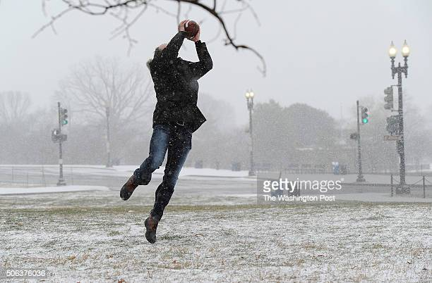 Chris Proctor catches a football as it snows near the Washington Monument as snow falls on Friday January 22 2016 in Washington DC A large snow event...