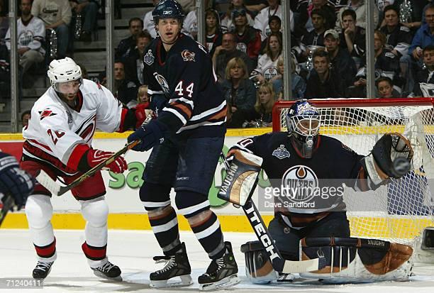 Chris Pronger of the Edmonton Oilers and Erik Cole of the Carolina Hurricanes battle for position as goaltender Jussi Markkanen prepares to make a...