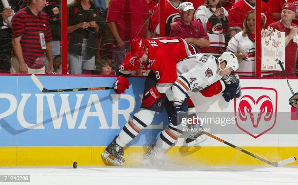 Chris Pronger of the Edmonton Oilers and Mark Recchi of the Carolina Hurricanes clash during game seven of the 2006 NHL Stanley Cup Finals on June...