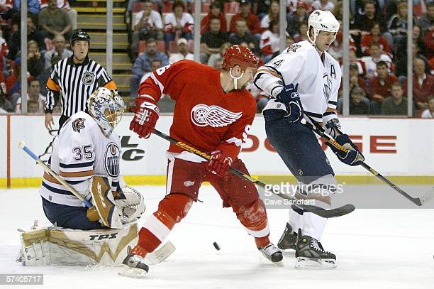 Chris Pronger of the Edmonton Oilers battles for position with Tomas Holmstrom of the Detroit Red Wings while Dwayne Roloson of the Edmonton Oilers...