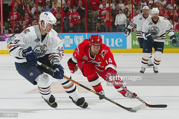 Chris Pronger of the Edmonton Oilers controls the puck against Kevyn Adams of the Carolina Hurricanes during game seven of the 2006 NHL Stanley Cup...