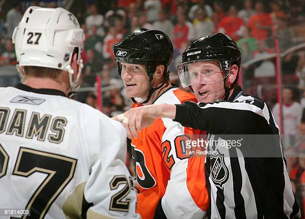 Chris Pronger of the Philadelphia Flyers is separated from Craig Adams of the Pittsburgh Penguins by linesman Jean Morin on October 8 2009 at the...