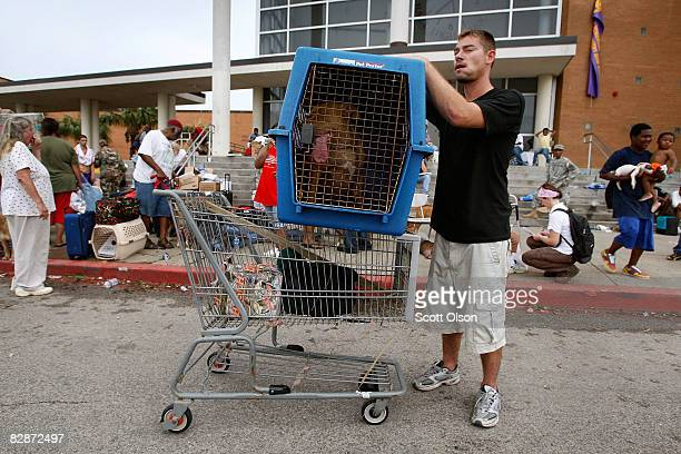 Chris Ragle with his dog Diesel arrive at an evacuation center after his home was damaged by Hurricane Ike September 14 2008 in Galveston Texas Ike...