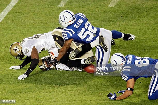 Chris Reis and Roman Harper of the New Orleans Saints fight for the ball with Cody Glenn and Hank Baskett of the Indianapolis Colts after a onside...