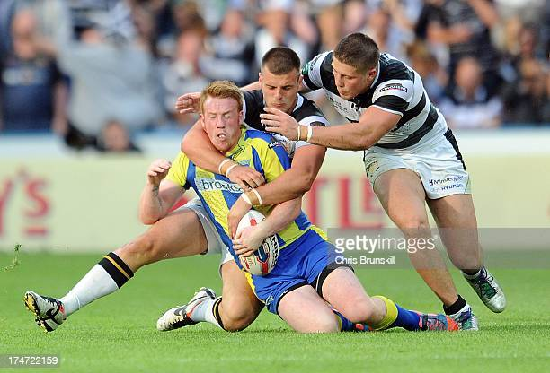 Chris Riley of Warrington Wolves is tackled by Joe Arundel and Jacob Miller of Hull FC during the Tetley's Challenge Cup Semi Final between Hull FC...