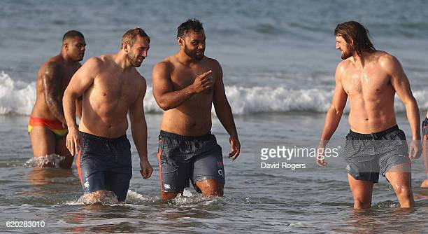 Chris Robshaw and Billy Vunipola talk to team mate Tom Wood as they walk up the beach after having had a swim in the Atlantic Ocean during the...