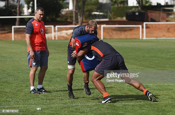 Chris Robshaw is tackled by team mate Billy Vunipola as Jason Ryles the former Australian rubgy league player who has been brought in as assistant...