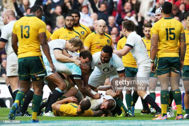 Chris Robshaw of England is congratulated by teammates after scoring his team's first try during the QBE International match between England and...