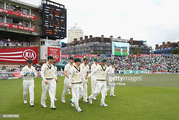 Chris Rogers and Michael Clarke of Australia lead the team onto the ground after the rain delay during their final test match during day four of the...