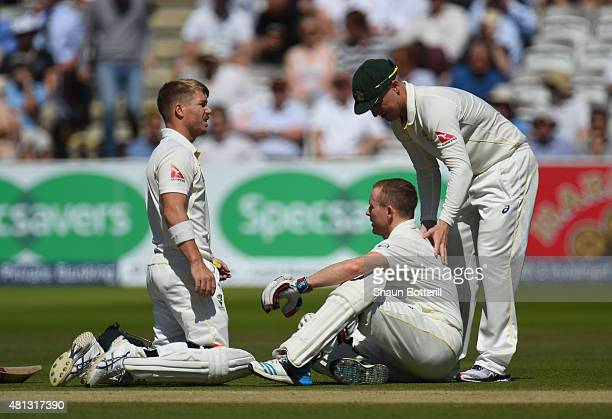 Chris Rogers of Australia is attended to by teammates David Warner and Brad Haddin after a dizzy spell during day four of the 2nd Investec Ashes Test...