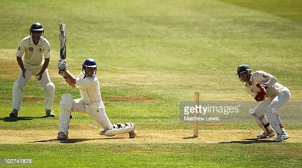 Chris Rogers of Derbyshire hits the ball towards the boundary as Simon Katich and Tim Paine of Australia look on during Day Two of the Warm up match...