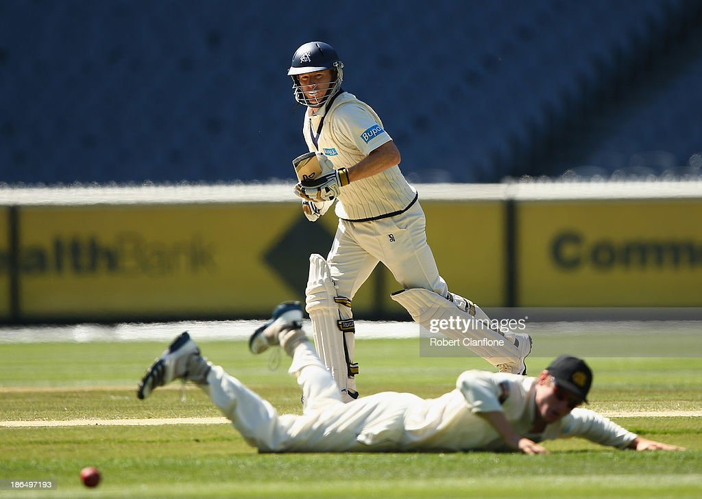 Chris Rogers of the Bushrangers gets the ball past Cameron Bancroft of the Warriors during day three of the Sheffield Shield match between the Victoria Bushrangers and the Western Australia Warriors at Melbourne Cricket Ground on November 1, 2013 in Melbourne, Australia.