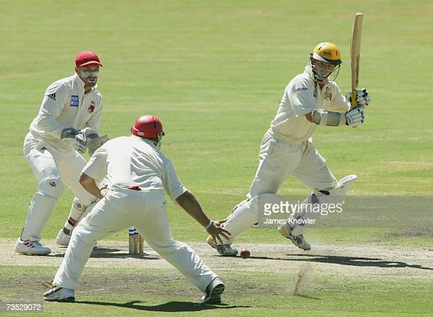 Chris Rogers of the Warriors hits the ball past Mark Cosgrove of the Redbacks during day two of the Pura Cup match between the South Australian...