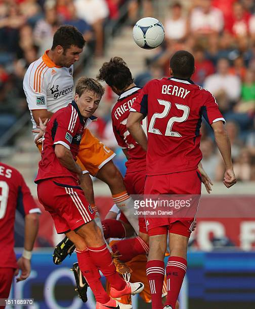 Chris Rolfe Arne Friedrich and Austin Berry of the Chicago Fire leap in front of the goal to keep the ball away from Will Bruin of the Houston Dynamo...