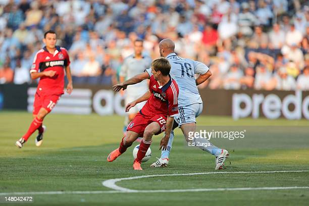 Chris Rolfe of Chicago Fire and Aurelien Collin of Sporting Kansas City vie for the ball in the first half at Livestrong Sporting Park on June 29...