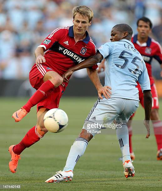 Chris Rolfe of Chicago Fire tries to pass around Julio Cesar of Sporting Kansas City in the first half at Livestrong Sporting Park on June 29 2012 in...