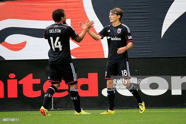 Chris Rolfe of DC United celebtrates after scoring a goal against the Houston Dynamo with teammate Nick DeLeon during the first half at RFK Stadium...