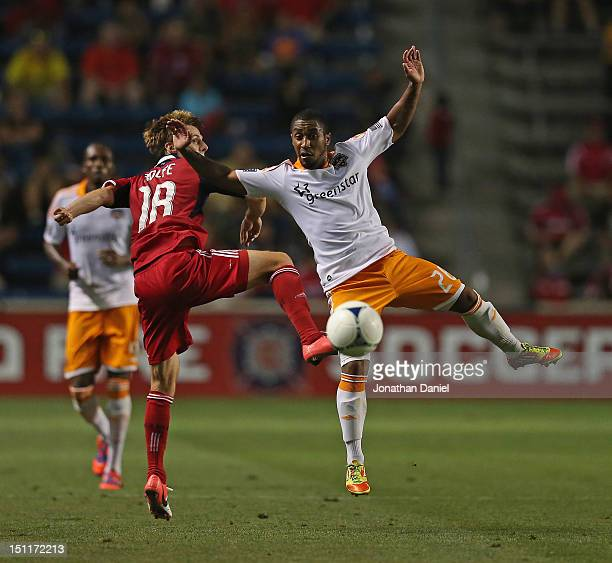 Chris Rolfe of the Chicago Fire and Corey Ashe of the Houston Dynamo leap and battle for the ball during an MLS match at Toyota Park on September 2...