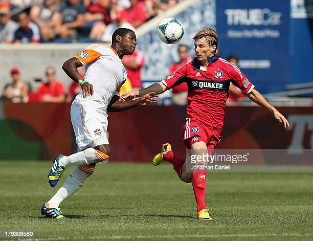Chris Rolfe of the Chicago Fire and Kofi Sarkodie of the Houston Dynamo battle for the ball during an MLS match at Toyota Park on September 1 2013 in...