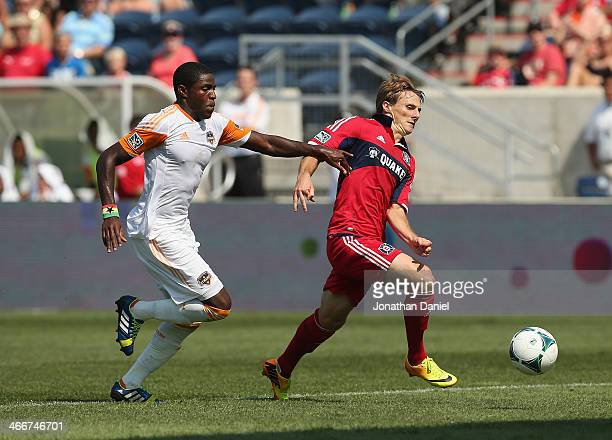 Chris Rolfe of the Chicago Fire battles with Kofi Sarkodie of the Houston Dynamo during an MLS match at Toyota Park on September 1 2013 in Bridgeview...