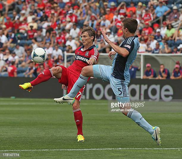 Chris Rolfe of the Chicago Fire controls the ball under pressure from Matt Besler of Sporting Kansas City during an MLS match at Toyota Park on July...