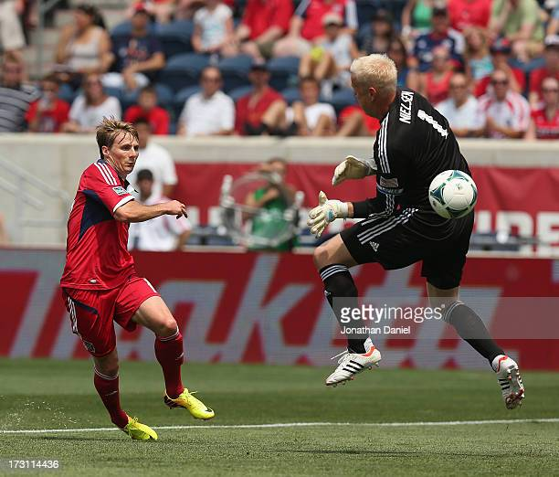 Chris Rolfe of the Chicago Fire fires a shot past Jimmy Nielsen of Sporting Kansas City during an MLS match at Toyota Park on July 7 2013 in...