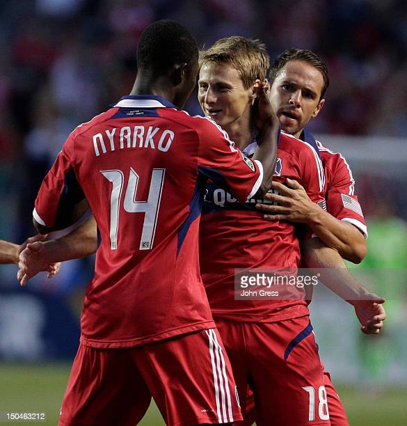 Chris Rolfe of the Chicago Fire is congratulated by teammate Patrick Nyarko after scoring a goal on the New England Revolution in the first half...
