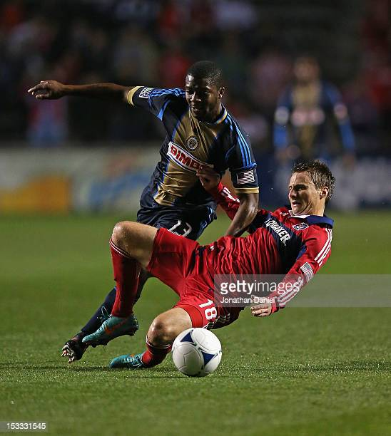 Chris Rolfe of the Chicago Fire is knocked down by Michael Lahoud of the Philadelphia Union during an MLS match at Toyota Park on October 3 2012 in...