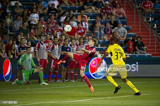 Chris Rolfe of the Chicago Fire kicks the ball away from Kevan George of the Columbus Crew at Toyota Park on June 23 2012 in Bridgeview Illinois The...