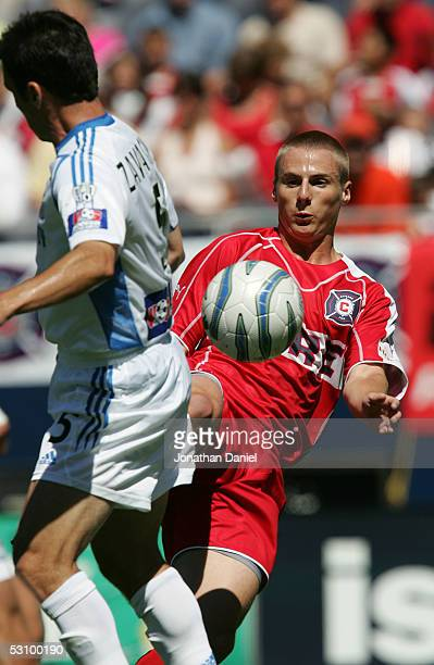 Chris Rolfe of the Chicago Fire kicks the ball past Kerry Zavagnin of the Kansas City Wizards on June 18 2005 at Soldier Field in Chicago Illinois...