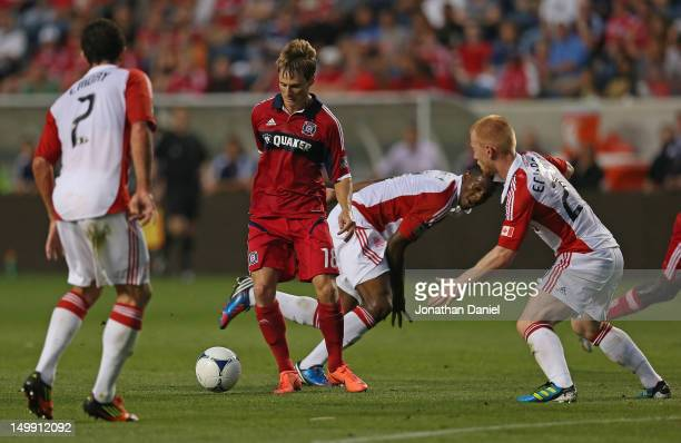 Chris Rolfe of the Chicago Fire moves to the ball under pressure from Richard Eckersley Ryan Johnson and Logan Emory of Toronto FC during an MLS...