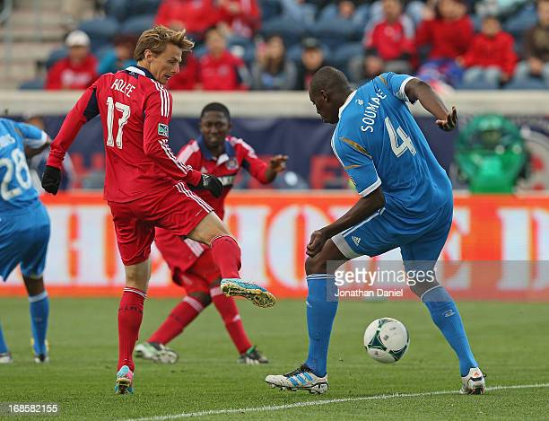 Chris Rolfe of the Chicago Fire passes around Bakary Soumare of the Philadelphia Union during an MLS match at Toyota Park on May 11 2013 in...