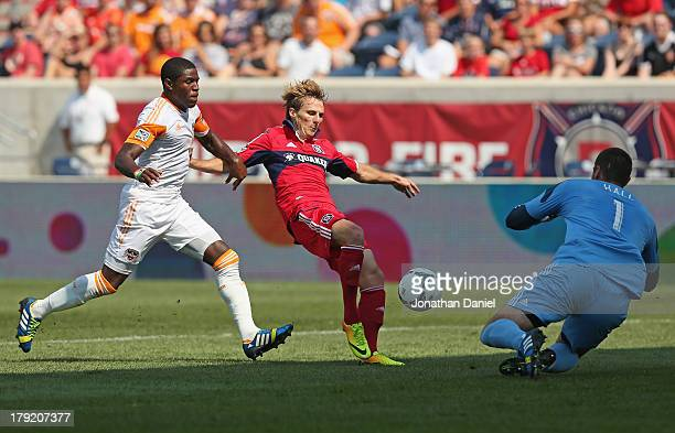 Chris Rolfe of the Chicago Fire takes a shot against Tally Hall of the Houston Dynamo as Kofi Sarkodie defends during an MLS match at Toyota Park on...
