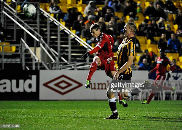Chris Rolfe of the Chicago Fire takes a shot on goal as Cody Ellison of the Charleston Battery looks on during the first half of a game at Blackbaud...
