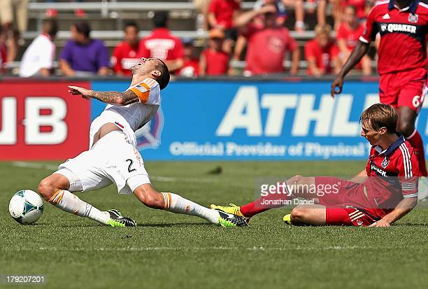 Chris Rolfe of the Chicago Fire takes down Eric Brunner of the Houston Dynamo during an MLS match at Toyota Park on September 1 2013 in Bridgeview...