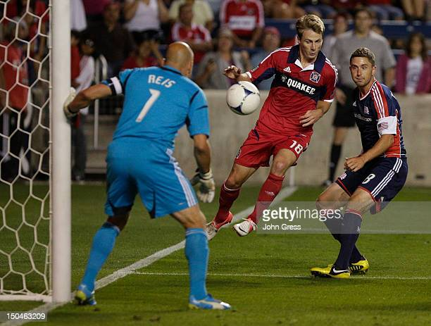Chris Rolfe of the Chicago Fire tries to score on Matt Reis of the New England Revolution and Chris Tierney in the first half during their MLS match...