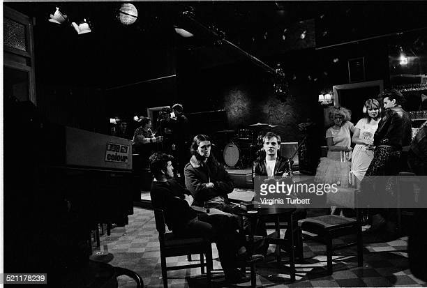 Chris Ryan as Mike Nigel Planer as Neil and Rik Mayall as Rick with members of the band Madness behind on set in front of a BBC camera during the...