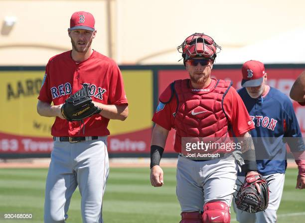 Chris Sale and Christian Vazquez of the Boston Red Sox walk to the dugout for the start of the spring training game against the Miami Marlins at...