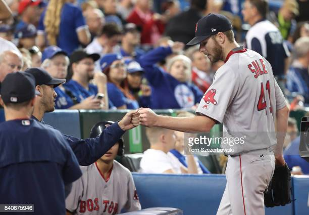 Chris Sale of the Boston Red Sox is congratulated by Rick Porcello as he returns to this dugout after retiring the side in the seventh inning during...