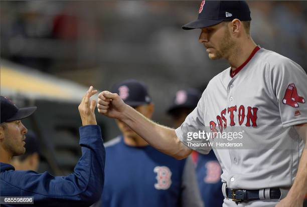Chris Sale of the Boston Red Sox is congratulated by teammates as he returns to the dugout after striking out his tenth batter of the game against...