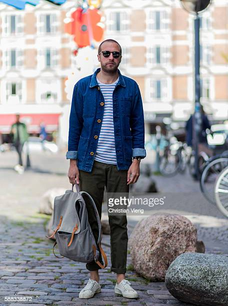 Chris Scholes wearing sunglasses a backpack a denim shirt a striped tshirt an olive pants and white court sneakers outside Revolver Fair during the...