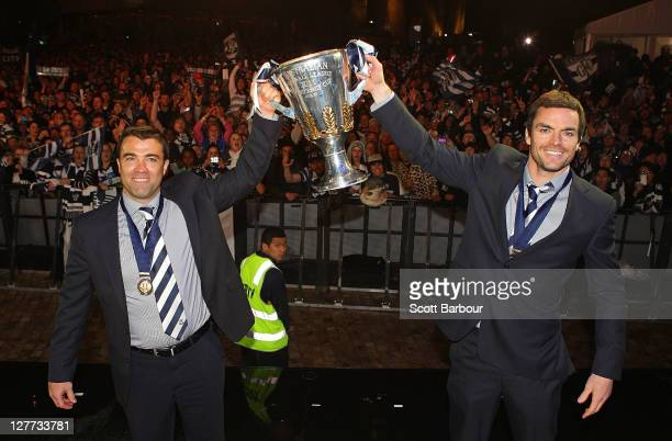Chris Scott coach and Matthew Scarlett of the Geelong Football Club pose with the Premiership Cup after the 2011 AFL Grand Final match between the...