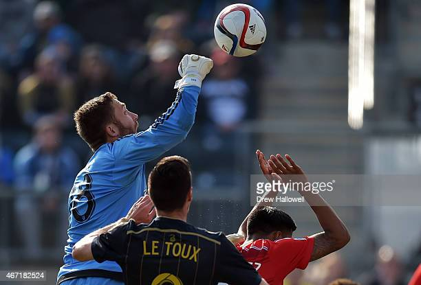 Chris Seitz of FC Dallas punches the ball away from Sebastien Le Toux of Philadelphia Union and teammate Moises Hernandez at PPL Park on March 21...