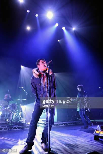 Chris Sharrock Liam Gallagher and Gem Archer of Beady Eye perform on stage at the Hammersmith Apollo on November 21 2013 in London England