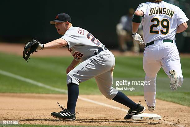 Chris Shelton of the Detroit Tigers fields as Dan Johnson runs during the game against the Oakland Athletics at the Network Associates Coliseum in...