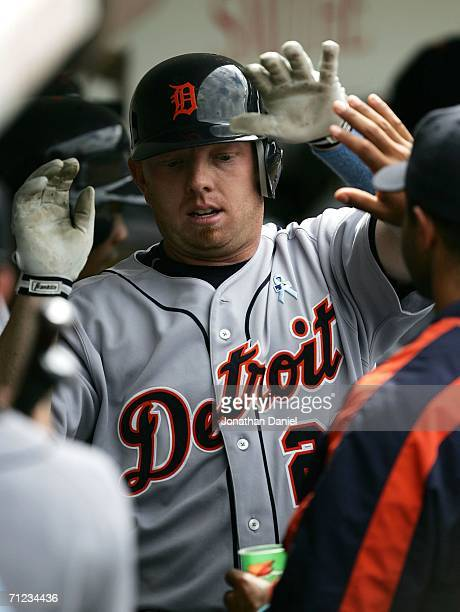 Chris Shelton of the Detroit Tigers is congratulated by teammates in the dugout after hitting his second home run of the game against the Chicago...