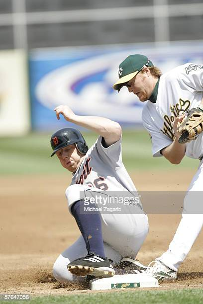 Chris Shelton of the Detroit Tigers slides into first base against Dan Johnson of the Oakland Athletics at the Network Associates Coliseum in Oakland...