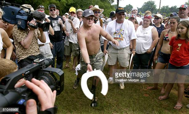 """Chris """"Skillet"""" Davison aims his plastic toilet seat at the target during the Redneck Horseshoe contest in the 9th Annual Summer Redneck Games July..."""